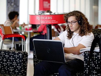 Male student sitting at computer listening to music