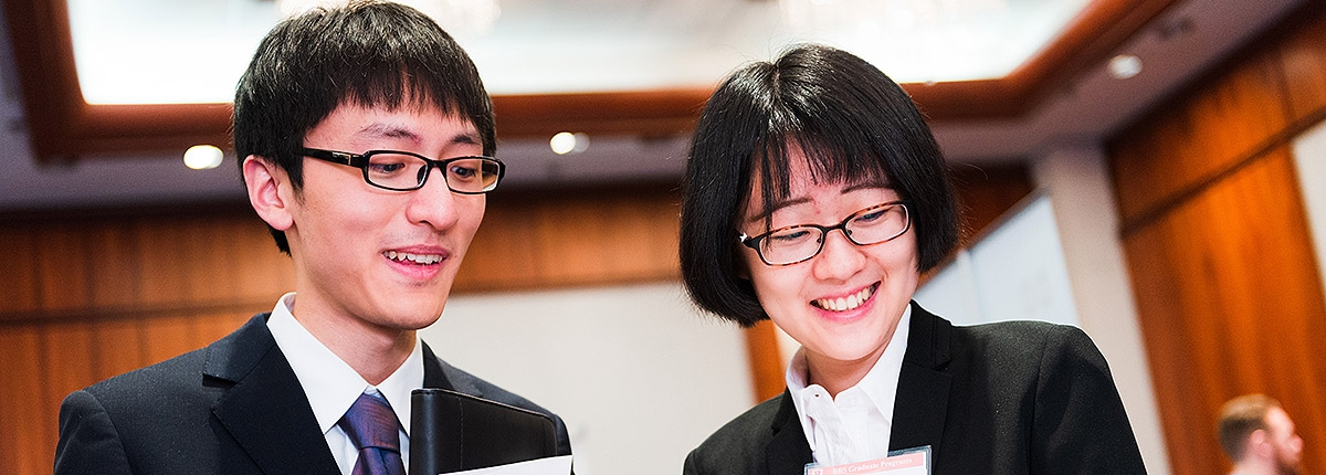 Two students looking through paperwork at a career fair