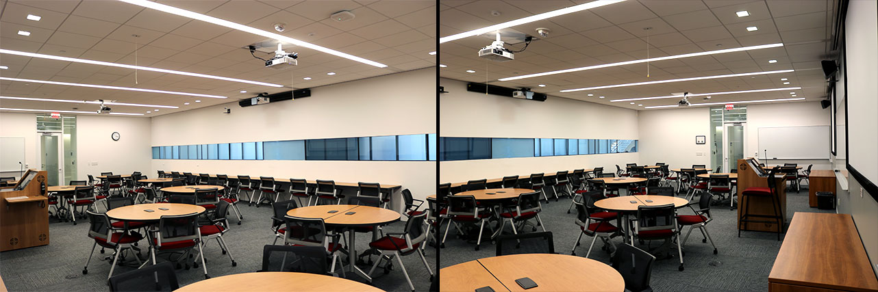 Classroom with round table and mobile chairs, a whiteboard, a podium, projection screens and a long table with chairs against the wall.